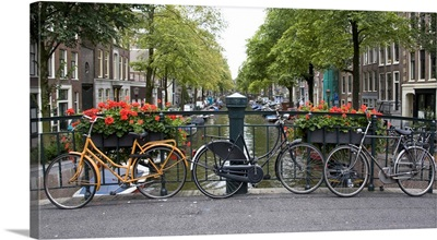 View from a bridge over a canal in Amsterdam with colorful bikes and red flowers