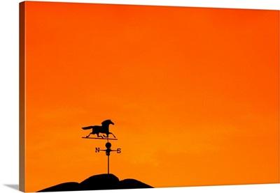Weathervane atop barn at sunset indicates wind direction