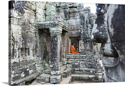 Cambodia, Siemreab, Angkor, Young monk sitting in a window at the Bayan Temple
