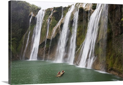 China, Yunnan, Luoping, Tourists on a bamboo raft in front of the Jiulong waterfalls