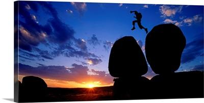 Devils Marbles National Park, man jumping on rocks