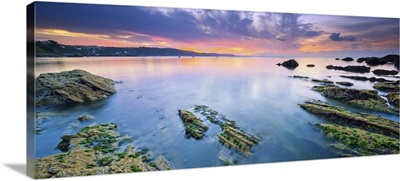 England, Cornwall, Rocks surfacing from the low tide seaside at dawn near Looe village