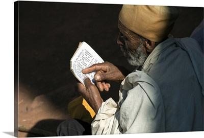 Ethiopia, Amhara, Lalibela, Monk reading Bible at Biete Abba Libanos