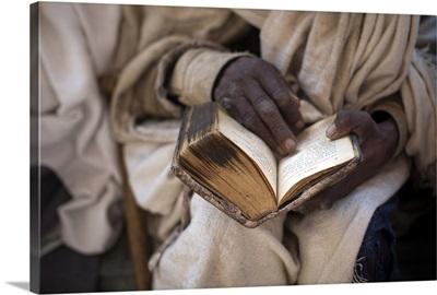 Ethiopia, Amhara, Lalibela, Priest reading an old Bible, Bete Maryam