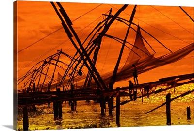 India, Kerala, Fishing net at sunset