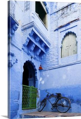 India, Rajasthan, Jodhpur, Bike resting against a wall of a blue house