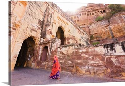 India, Rajasthan, Jodhpur, Woman in a colorful sari walking into Mehrangarh Fort