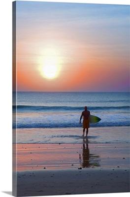 Indonesia, Bali, Jimbaran, Surfer on the beach at sunset