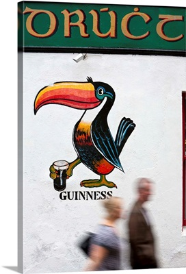 Ireland, Galway, People walk by a traditional Pub with Gaelic sign writing