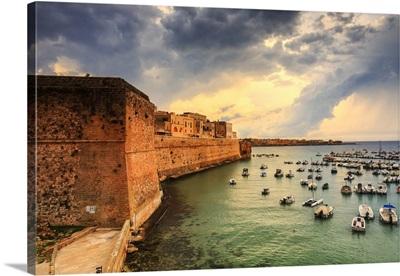 Italy, Apulia, Bastione dei Pelasgi, old town walls and the harbor at sunrise