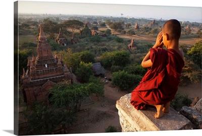 Myanmar, Bagan, A novice Buddhist monk prays on a temple at sunrise