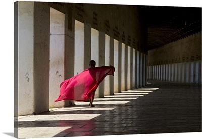 Myanmar, Bagan, Novice monk walking along the covered entrance to Schwezigon Paya