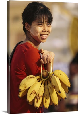 Myanmar, Burmese woman carrying bananas with decorative Thanaka Paste on her face