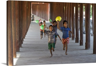Myanmar, Mandalay, Bagan, Local children running along a passage with balloons
