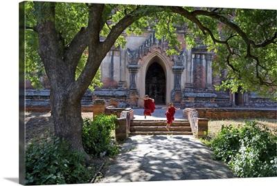 Myanmar, Mandalay, Bagan, Novice monks jumping down the steps of the Ananda temple