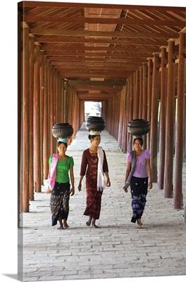 Myanmar, Mandalay, Bagan, Women walking along a passage carrying loads on their heads