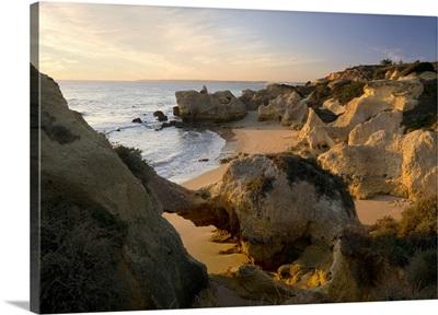 Portugal, Faro, Algarve, Albufeira, Small rocky cove near Albufeira at sunset