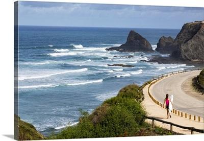 Portugal, Faro, Algarve, Surfer walking down the road along the sea