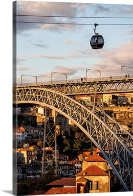 Portugal, Porto, Cable car over the bridge at sunset