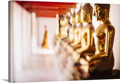 Thailand, Bangkok, Buddhist monk walking past a line of golden Buddha statues