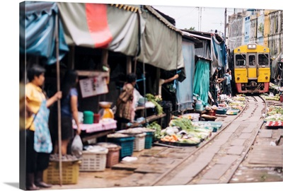 Thailand, Maeklong Railway Market, traders clearing the tracks as the train approaches