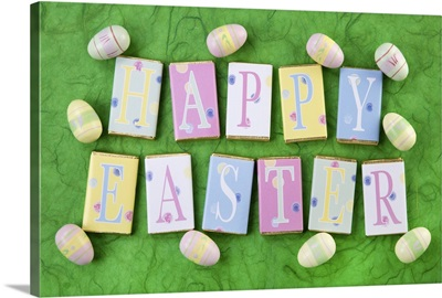 Row Of Chocolate Bars With Letters Spelling Happy Easter, With Small Easter Eggs
