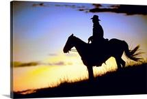 Silhouette of a cowboy on horseback at sundown.