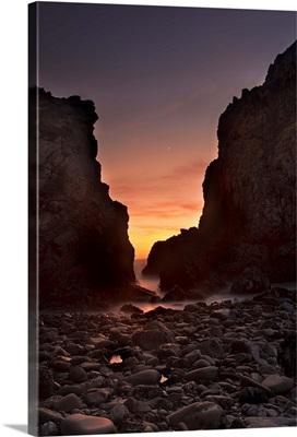 A crescent moon sets through a dusk-colored sky at Pfeiffer Beach, CA, USA