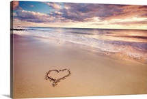 A heart in the sand on a Dutch beach during sunset.