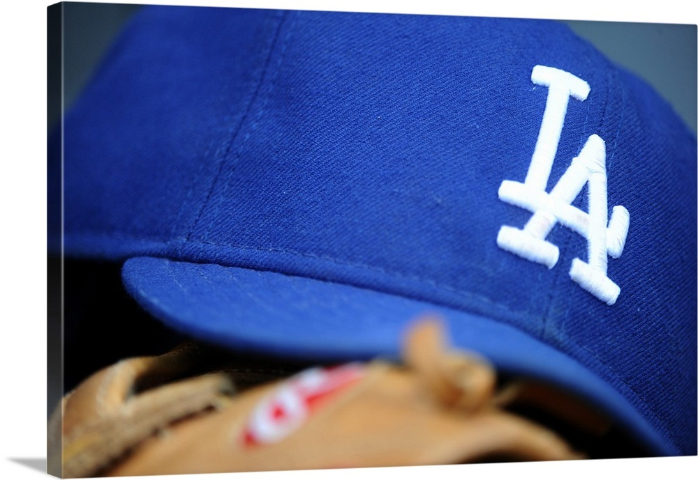 A Los Angeles Dodgers hat and glove rest in the dugout
