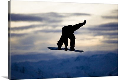 A male snowboarder does a backside 180 mute grab