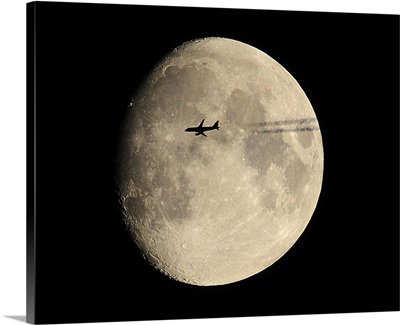 A plane in front of the moon