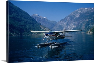 A seaplane lands on the blue waters of Geirangerfjord