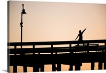 A silhouetted woman does a yoga pose on the Ventura Pier in Ventura, California.