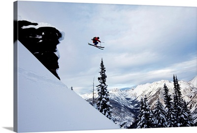A skier jumping off a cliff in the backcountry in Colorado.