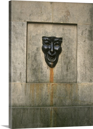 A smiling face wall fountain on the Royal Mile