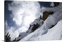 A snowboarder jumps off a cliff into powder in Colorado.