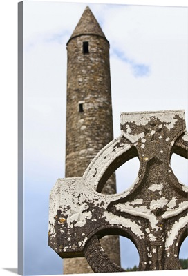 a tombstone in a cemetery and a round tower on a 6th century monastic site