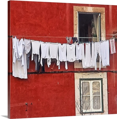 A window with a clothes drying on the clothesline in Lisbon, Portugal