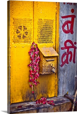 a yellow mailbox is draped with red flowers were left over from a puja
