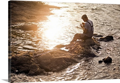 A young fisherman sitting on a rock.