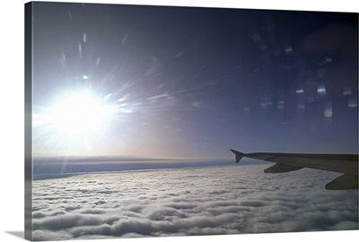 Airplane wing and sun above clouds