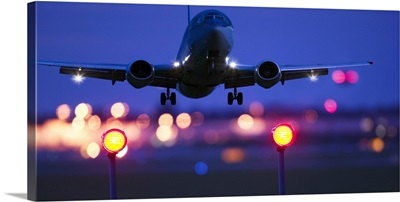 an airplane landing with blurred lights of the airport in the background
