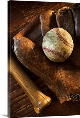 Antique baseball on baseball glove with bat
