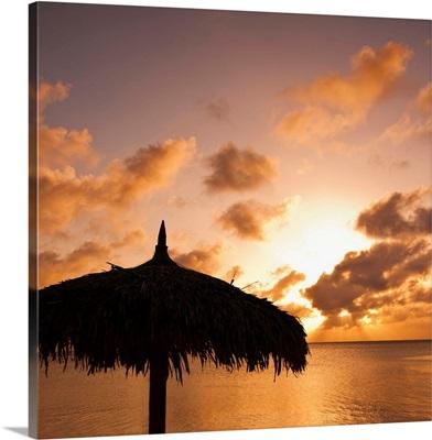 Aruba, silhouette of palapa on beach at sunset