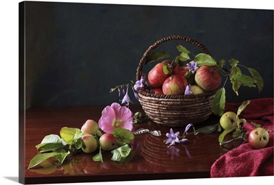 Basket of apples and blue flowers with reflection on table.