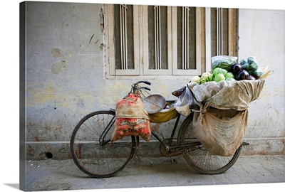 bicycle carrying vegetables leaning against a wall in nizamuddin