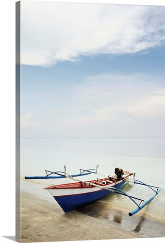 Blue, red and white wooden outrigger fishing boat on sandy beach ...