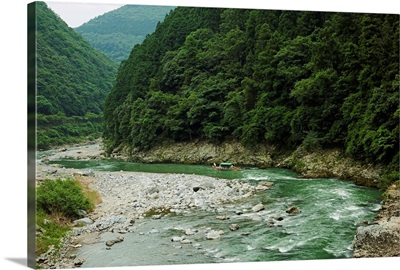 Boat floating down volcanic river gorge in lush green forest, Hozu Gorge, Kyoto, Japan.