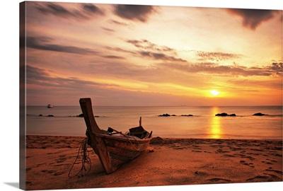 Boat on beach at sunset on Koh Lanta, Thailand.